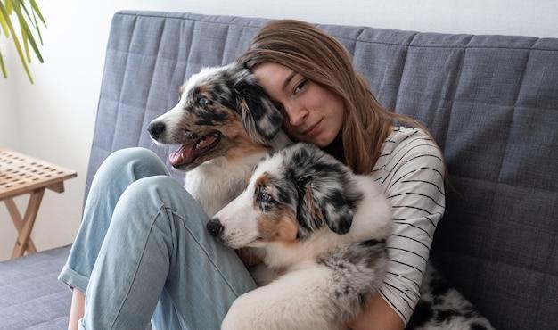 Atrakcyjna młoda kobieta obejmując dwa słodkie owczarek australijski blue merle szczeniak. siedząc na kanapie. koncepcja opieki nad zwierzętami. miłość między człowiekiem a zwierzęciem.