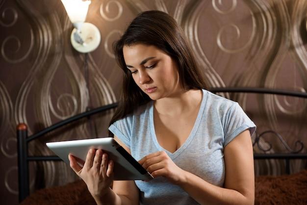 Atrakcyjna młoda kobieta, patrząc na jej cyfrowy tablet, siedząc na łóżku w domu.