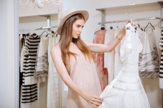 Atrakcyjna młoda kobieta, patrząc na piękną białą sukienkę i myślenia w sklepie odzieżowym