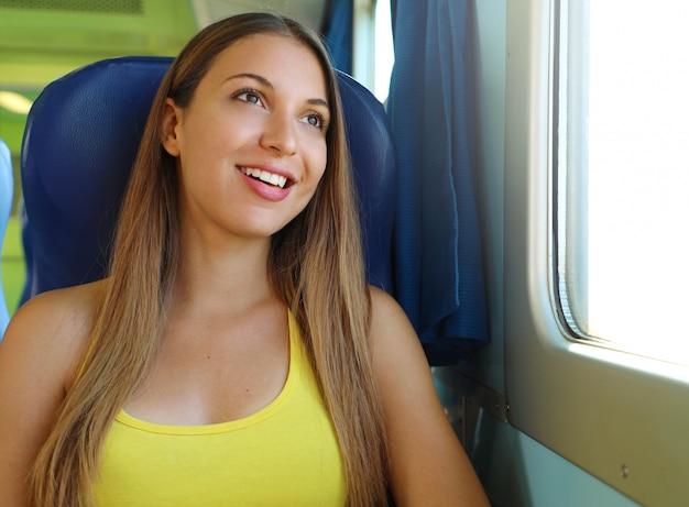 Atrakcyjna młoda kobieta, patrząc przez okno pociągu lub autobusu. szczęśliwy pasażer pociągu podróżujący siedzi na siedzeniu i patrząc przez okno.