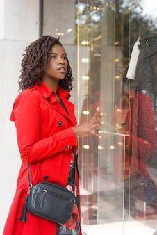 Atrakcyjna młoda kobieta patrzeje gablotę wystawową