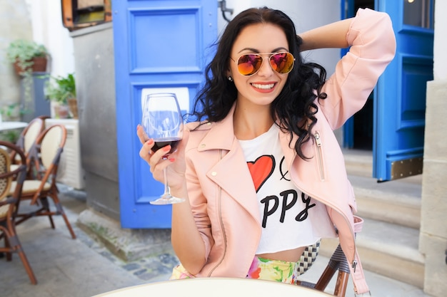 Atrakcyjna młoda kobieta pije wino na letnie wakacje siedząc w miejskiej kawiarni ulicy w fajny strój