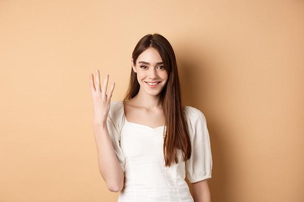 Atrakcyjna młoda kobieta pokazuje palce numer cztery, uśmiecha się i wygląda pewnie, stojąc na beżu.