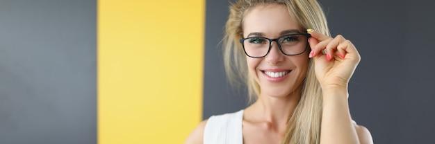 Atrakcyjna młoda kobieta poprawia okulary i śmieje się portret pięknej młodej kobiety w