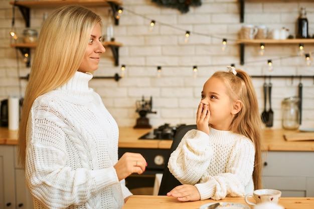 Atrakcyjna młoda kobieta pozuje w stylowym, przytulnym wnętrzu kuchni ozdobionym girlandą, zabierając się do swojej uroczej dziewczynki, która wyraża zdziwienie, podekscytowana nieoczekiwanymi pozytywnymi wiadomościami, zakrywając usta