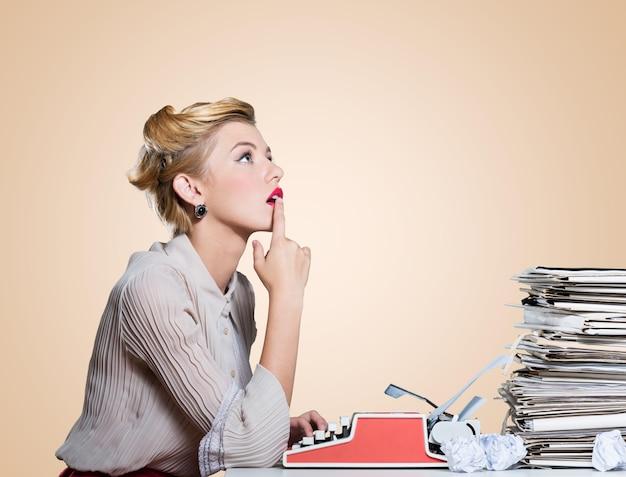 Atrakcyjna młoda kobieta pracująca na zabytkowej maszynie do pisania