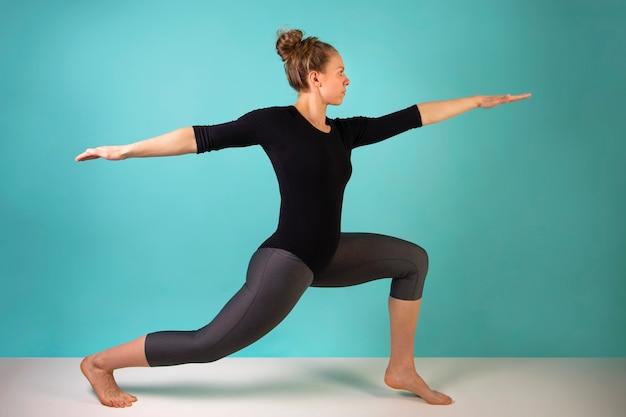 Atrakcyjna młoda kobieta pracuje na niebieskim tle. wysportowana kobieta robi ćwiczenia. siła i motywacja, sport i zdrowy tryb życia, zasady dbania o kondycję. kobieca sprawność.