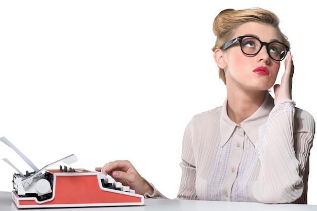 Atrakcyjna młoda kobieta pracuje na vintage maszynie do pisania na tle