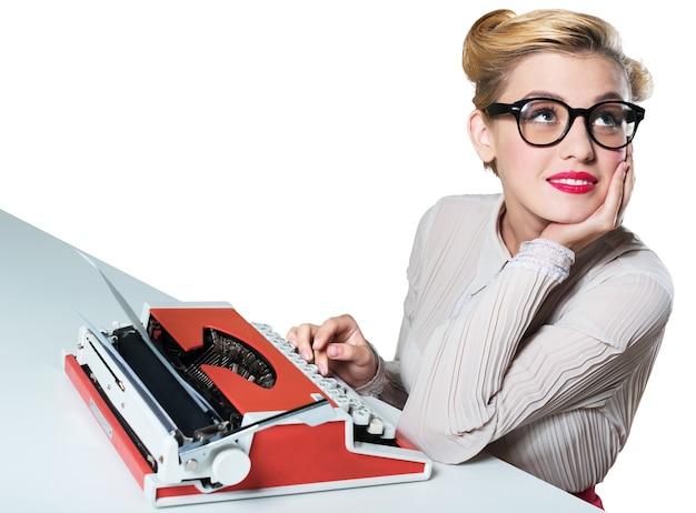 Atrakcyjna młoda kobieta pracuje na zabytkowej maszynie do pisania na białym tle