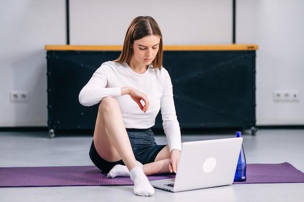 Atrakcyjna młoda kobieta przygotowuje się do ćwiczeń jogi, szukając na laptopie filmu z zawodu