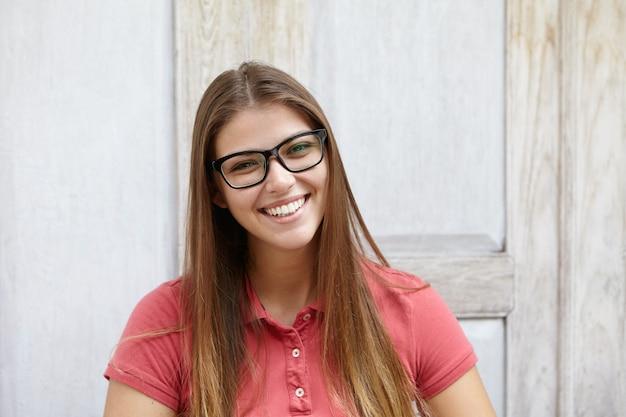 Atrakcyjna młoda kobieta rasy kaukaskiej w stylowe okulary prostokątne pozowanie w pomieszczeniu przed drewnianą ścianą
