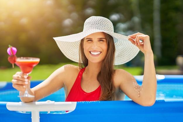 Atrakcyjna młoda kobieta relaksuje się na basenie na podwórku