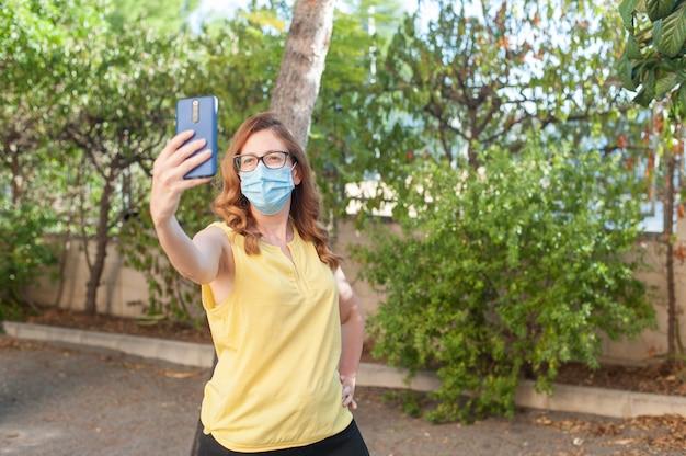 Atrakcyjna młoda kobieta robi selfie ze swoim smartfonem w parku podczas noszenia masek na twarz z powodu t