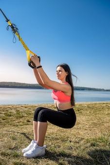 Atrakcyjna młoda kobieta robi trening trx na świeżym powietrzu w pobliżu jeziora w ciągu dnia. zdrowy tryb życia