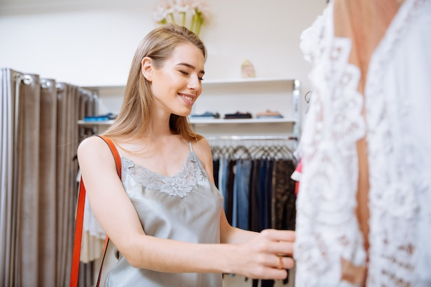 Atrakcyjna młoda kobieta robi zakupy i wybiera ubrania w sklepie odzieżowym