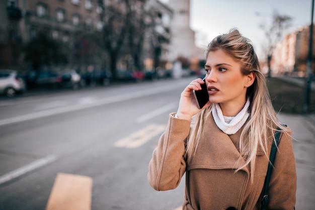 Atrakcyjna młoda kobieta rozmawia inteligentny telefon w mieście.