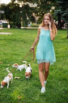 Atrakcyjna młoda kobieta rozmawia przez telefon komórkowy podczas spacerów z psami w parku