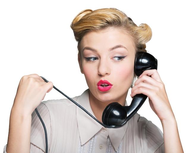 Atrakcyjna młoda kobieta rozmawia przez telefon vintage