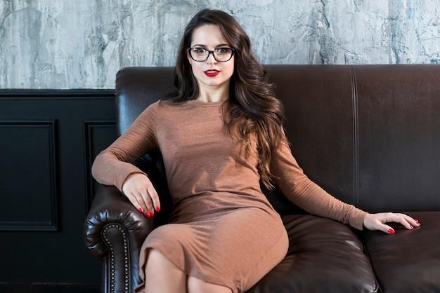 Atrakcyjna młoda kobieta siedzi na kanapie patrząc na kamery