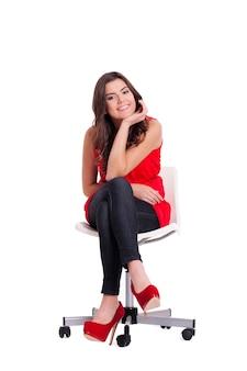 Atrakcyjna młoda kobieta siedzi na krześle