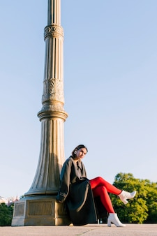 Atrakcyjna młoda kobieta siedzi pod filarem z jej skrzyżowanymi nogami
