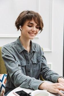 Atrakcyjna młoda kobieta siedzi przy stoliku w kawiarni w pomieszczeniu, pracując na laptopie, analizując dokumenty
