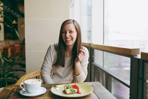 Atrakcyjna młoda kobieta siedzi sama w pobliżu duże okno w kawiarni przy stole z filiżanką cappuccino, ciasto, relaks w restauracji w czasie wolnym. młoda kobieta po odpoczynku w kawiarni. koncepcja stylu życia.