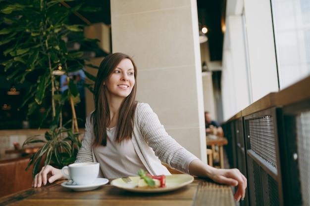 Atrakcyjna młoda kobieta siedzi samotnie w pobliżu duże okno w kawiarni przy stole z filiżanką cappuccino, ciasto, relaks w restauracji w czasie wolnym. młoda kobieta po odpoczynku w kawiarni. koncepcja stylu życia.