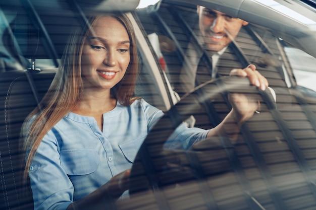 Atrakcyjna młoda kobieta siedzi w nowym samochodzie w salonie