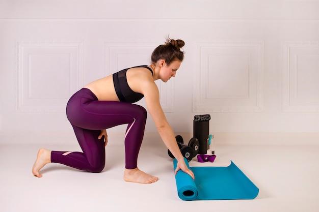 Atrakcyjna młoda kobieta składana niebieski mata do jogi lub fitness do ćwiczeń. siła i motywacja, sport i zdrowy tryb życia, zasady dbania o kondycję. kobieca sprawność. białe studio na poddaszu. strzał poziomy.