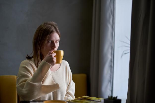 Atrakcyjna młoda kobieta spędza wolny czas siedząc w kawiarni, delektując się świeżą kawą i czytając magazyn dla kobiet.