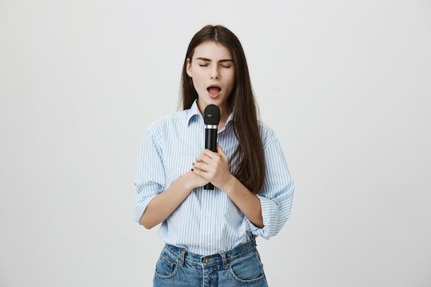 Atrakcyjna młoda kobieta śpiewa z zamkniętymi oczami z mikrofonem