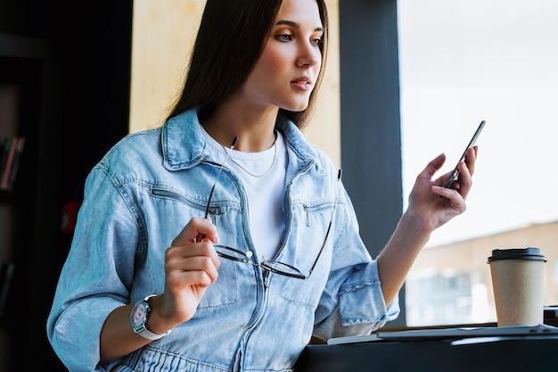 Atrakcyjna młoda kobieta stoi przy oknie, trzyma w ręku smartfon, okulary do widzenia i pracuje na laptopie.