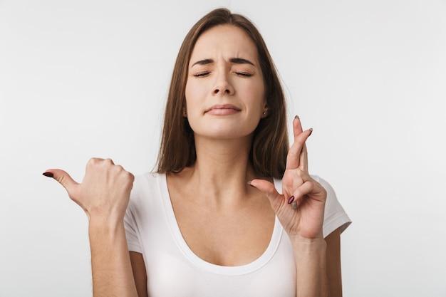 Atrakcyjna młoda kobieta stojąca na białym tle nad białą ścianą, trzymająca skrzyżowane palce na szczęście