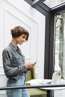 Atrakcyjna młoda kobieta stojąca w kawiarni w pomieszczeniu, przy użyciu telefonu komórkowego
