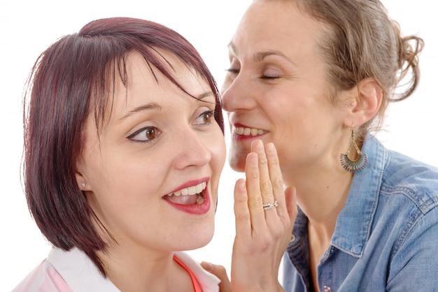 Atrakcyjna młoda kobieta szepcze sekret do ucha przyjaciela