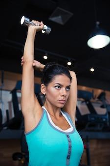 Atrakcyjna młoda kobieta treningu z hantlami w siłowni