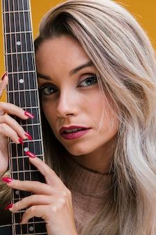 Atrakcyjna młoda kobieta trzyma gitarę na żółtym tle