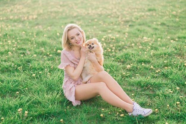 Atrakcyjna młoda kobieta trzyma psa szpic na zewnątrz i uśmiecha się do kamery, spacery w parku.