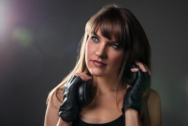 Atrakcyjna młoda kobieta trzyma słuchawki.