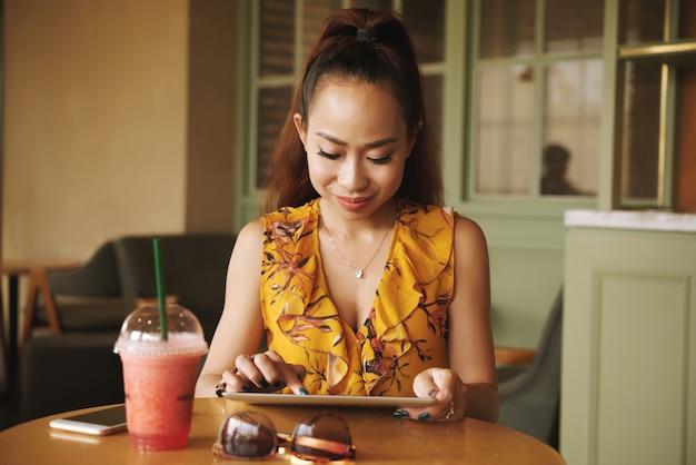 Atrakcyjna młoda kobieta używa app na pastylka komputerze