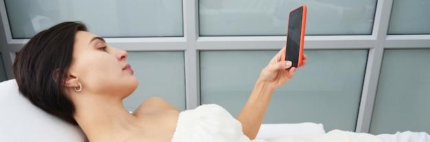 Atrakcyjna młoda kobieta używa smartphone i texting podczas gdy kłaść na masażu łóżku przy zdrojem