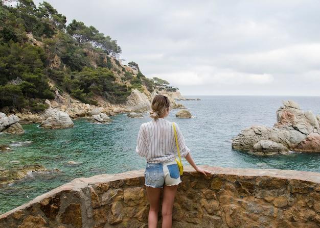 Atrakcyjna młoda kobieta w białej koszuli iz żółtą torbą, patrząc na morze w słoneczny dzień. szczupła dziewczyna w białej koszuli stoi na tle falującego morza i pięknych skał w hiszpanii, lloret de mar.
