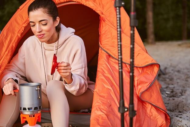 Atrakcyjna młoda kobieta w bluzie przygotowuje śniadanie i uśmiecha się siedząc w namiocie obozowym