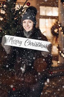 Atrakcyjna młoda kobieta w ciepłym ubraniu stoi pod śniegiem i życzy wszystkim wesołych świąt