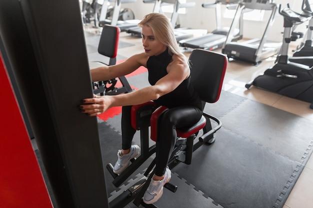 Atrakcyjna młoda kobieta w czarnej odzieży sportowej w białych trampkach ćwiczy siedząc na nowoczesnym symulatorze w siłowni