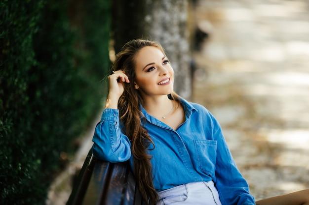 Atrakcyjna młoda kobieta w czarnych okularach, siedząc w letnim parku na ławce