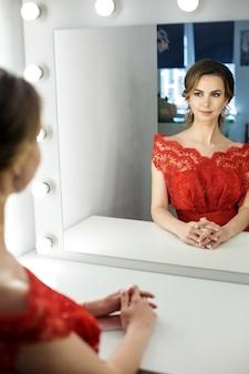 Atrakcyjna młoda kobieta w czerwonej sukience jest przygotowywana w garderobie
