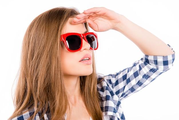 Atrakcyjna młoda kobieta w czerwonych okularach szuka sposobu