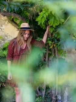 Atrakcyjna młoda kobieta w kapeluszu i sukience stojąca w pobliżu pięknych zielonych roślin